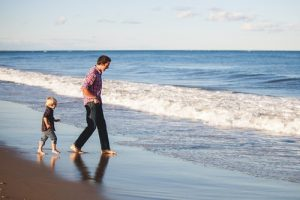 Man walks with child at beach. Men and relationships with their children can be beautiful and complex.