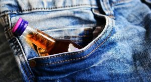 Bottle of alcohol in jeans pocket. Addictions can take over your work life, relationships, and health.